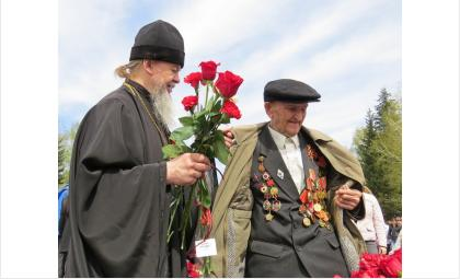 Фронтовику Алексею Никулину помогает 9 мая 2014 года снять куртку сын фронтовика - священник Василий Бирюков
