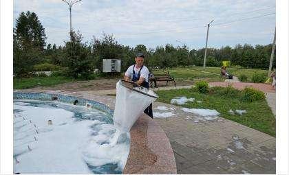 Парковый рабочий Александр Пасюк сачком вычерпывает из фонтана пену