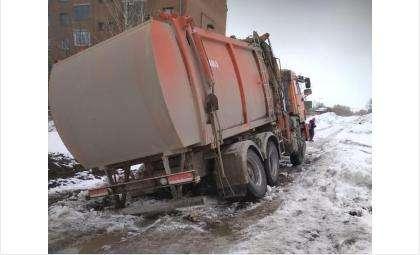 КамАЗ-мусоровоз забуксовал в глине и снегу на ул. Новой в Бердске