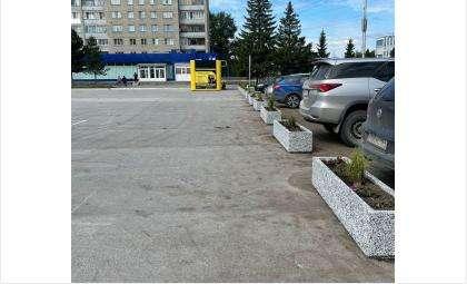 Ряд кашпо отделяет площадь от парковки