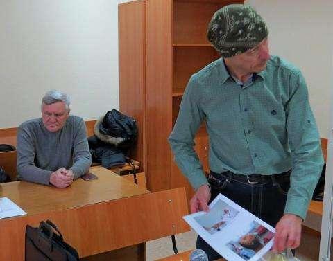В руках Владимира Вакракуты сделанные в больнице фотографии его травм, полученных от нападения стаи немецких овчарок. На заднем плане собаковод Борис Напольских